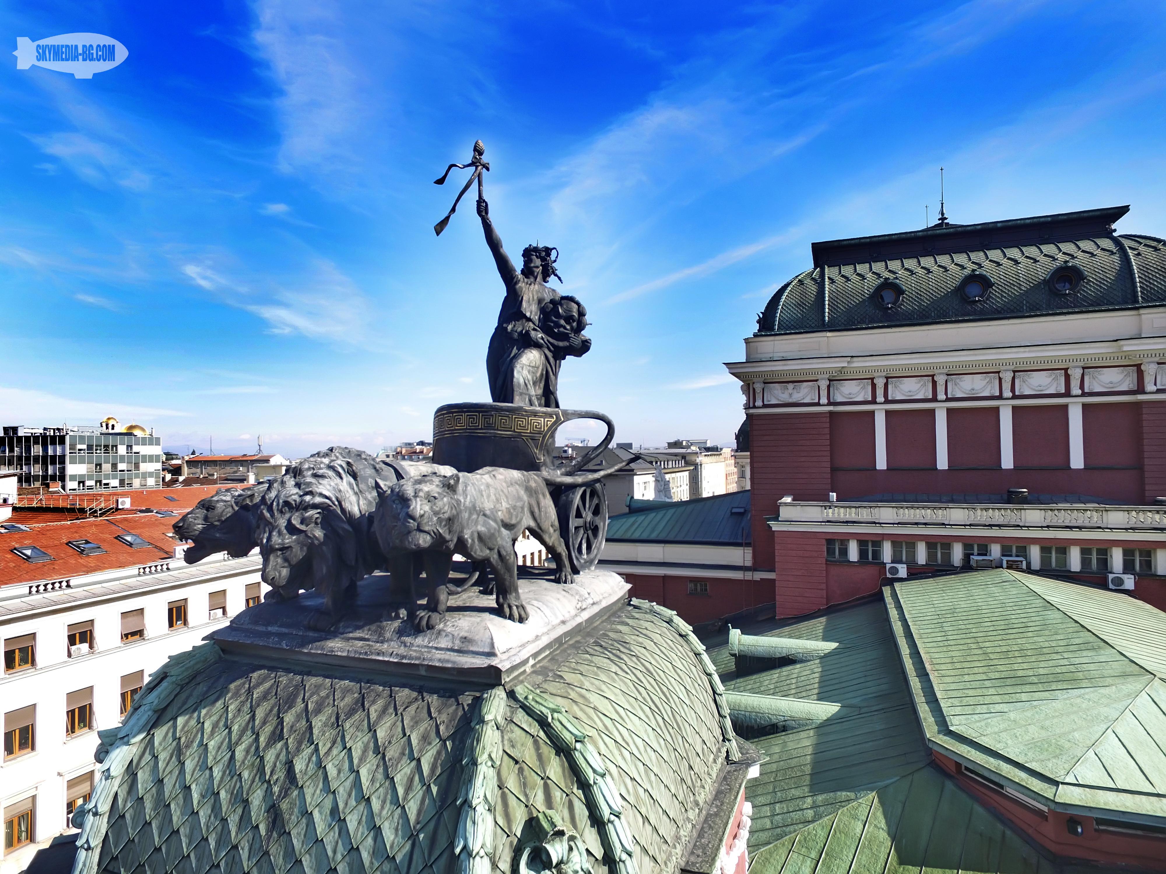 """Народният театър """"Иван Вазов"""" е завършен през 1906 г. по проект на виенските архитекти Херман Хелмер и Фердинанд Фелнер. Това е едната от двете метални композиции над предната фасада на театъра"""